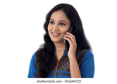 Happy young woman talking on cellphone against white background