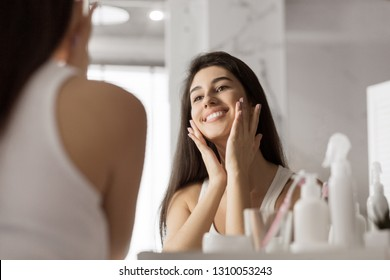 Happy young woman touching her face with hands , standing in bathroom, reflecting in mirror.