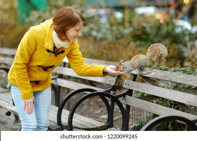 Happy young woman tourist feeding a squirrel in Madison Square Park, New York City, at sunny spring day. Female traveler enjoying views of downtown Manhattan. Travelling in USA.