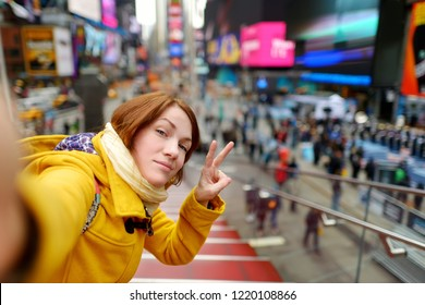 Happy young woman tourist sightseeing at Times Square in New York City. Female traveler taking selfies with her smartphone in downtown Manhattan. Travelling in USA.
