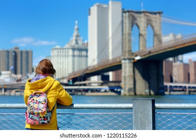 Happy young woman tourist sightseeing by Brooklyn Bridge, New York City, at sunny spring day. Female traveler enjoying view of downtown Manhattan. Travelling in USA.