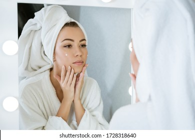 A happy young woman in a towel in front of a mirror applies cream to her face, a concept of skin care at home.