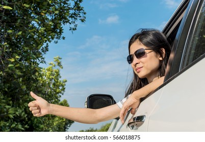 Happy young woman travel vacation leaning out car window on blue sky background.