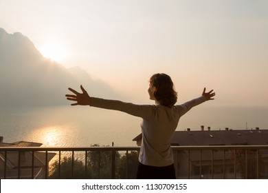 Happy young woman traveler outstretching arms feeling free, motivated looking at sunrise, sky over mountains, peaceful sea, enjoying scenic view, vacation concept. Italy, Lombardia, Riva di Solto