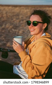 Happy young woman traveler in sunglasses holding iron mug cup with tea or coffee, enjoying sunset scenery in nature landscape, sitting in camp.Travel camping and adventure lifestyle concept. Vertical