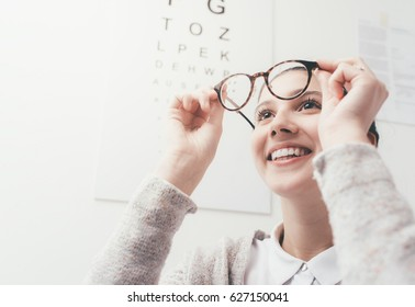Happy young woman trying her new glasses, eye care concept
