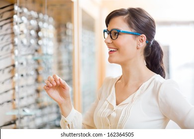 Happy young woman trying new glasses at optician store