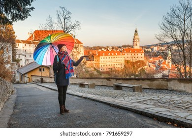 Happy young woman with umbrella travelling in Cesky Krumlov at winter