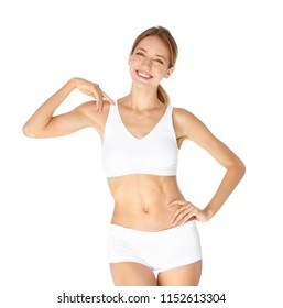 Happy young woman in underwear satisfied with her diet results, isolated on white