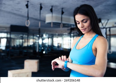 Happy young woman using activity tracker in fitness gym