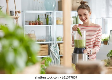 Happy young woman using blender to prepare a smoothie