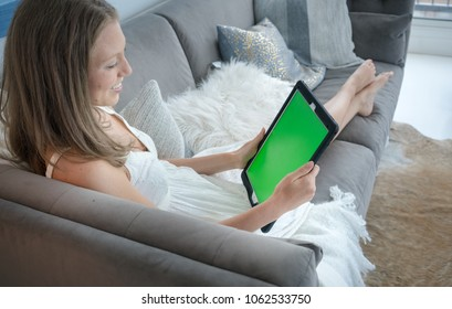 Happy young woman using digital tablet on sofa in living room