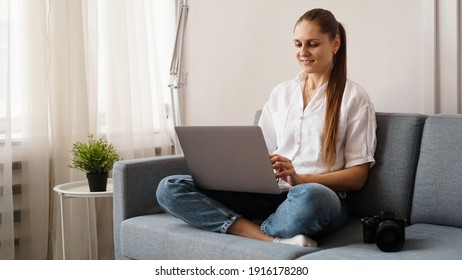 Happy young woman using laptop at home. On the couch next to the woman is a camera. Photographer retouches photographs at home.