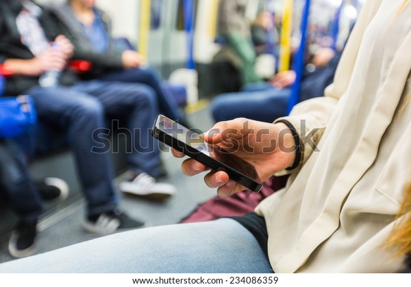 Happy Young Woman Using Mobile Phone in the Tube