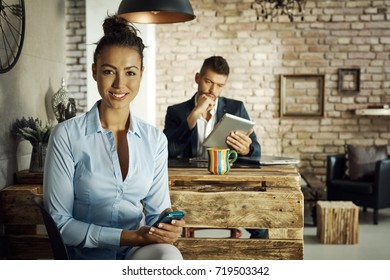Happy young woman using mobilephone at home.