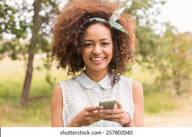 Happy young woman using smartphone on a sunny day