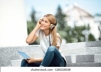 Happy young woman with vintage music headphones and a take away coffee cup, surfing internet on tablet pc, listening to the music and sitting on stairs against urban city background.