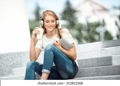 Happy young woman with vintage music headphones, holding a take away coffee cup and tablet pc, sitting on stairs against urban city background.
