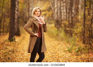 Happy young woman walking in autumn park Stylish blond fashion model wearing classic beige coat and pink scarf