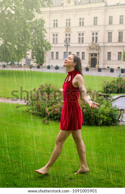 Happy young woman walking barefoot on the green grass in the rain, city park with historic building on the background, she has open arms and walking forward, smile and positive emotions, Valtice