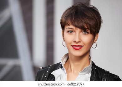 Happy young woman walking in city street. Stylish fashion model with pixie hair wearing black leather jacket