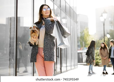 Happy young woman walking in the street with dog and shopping bags