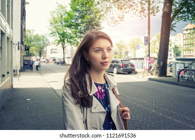 Happy young woman walking in the streets of European cities.