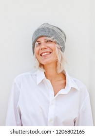 Happy young woman in warm grey beanie wool knitted hat.