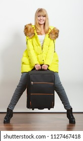Happy young woman in warm jacket carrying heavy suitcase. Gorgeous blonde tourist travel girl. Tourism.