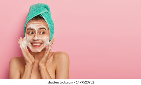 Happy young woman washes face with genlte cleanser, applies exfolaition soap scrub for having delicate skin, removes daily routine and takes bath, stands with naked body against pink studio wall