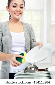 Happy Young Woman Washing Dishes in the kitchen