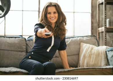 Happy young woman watching tv in loft apartment