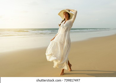 Happy young woman wearing beautiful white dress is walking on the beach during sunset