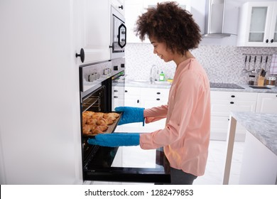A Happy Young Woman Wearing Blue Mitt Removing Baked Croissants Tray From An Oven