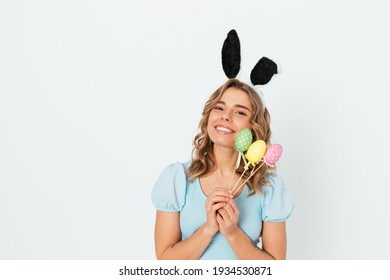 Happy young woman wearing bunny ears celebrating Easter holiday holding decorative colorful eggs smiling standing on white studio background with copy space.
