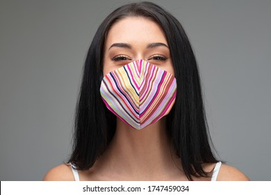 Happy young woman wearing a colorful face mask looking at the camera with smiling eyes in a concept of a post Covid-19 lifestyle reality over a grey background
