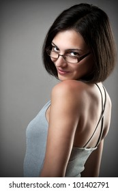Happy young woman wearing eyeglasses looking to the camera on grey background