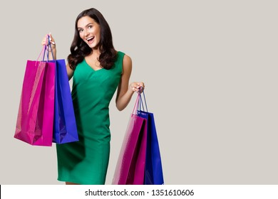 Happy young woman wearing green dress standing isolated over Gray background, carrying shopping bags  - Image