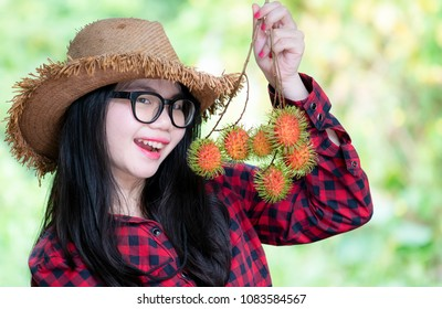 Happy young woman wearing red plaid shirt and hat holding rambutan fruit on her hand,Ripe rambutan on basket/colorful yellow fruit for sale/fruit trade products in local market/marketing of rambutan,