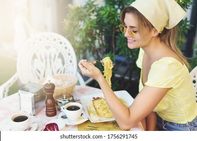 Happy young woman wearing stylish clothes is  eating pasta in Italian restaurant