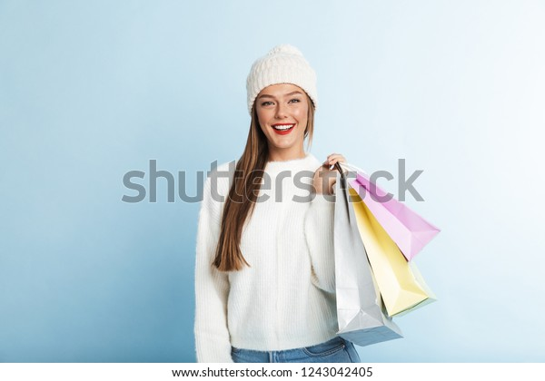 Happy young woman wearing sweater standing isolated over blue background, carrying shopping bags