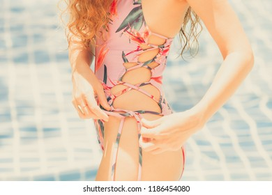 Happy young woman wearing swimsuit having good time at swimming pool in luxury resort. Summer travel holiday concept.