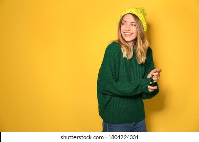 Happy young woman wearing warm sweater and knitted hat on yellow background. Space for text