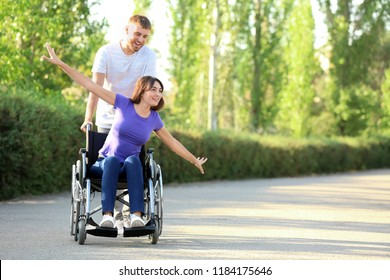 Happy young woman in wheelchair and her husband outdoors