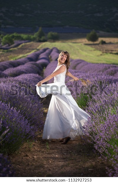 Happy young woman in a white dress in a lavender field