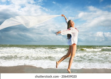 Happy young woman with white fabric at the beach. Freedom concept