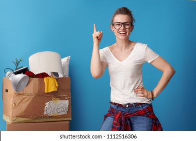 happy young woman in white shirt got idea and an untidy cardboard box in the background isolated on blue