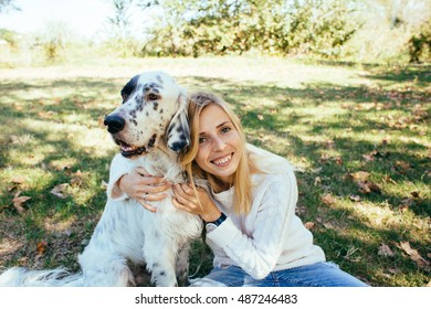 happy young woman in a white sweater and blue jeans hugging a big white dog in the park