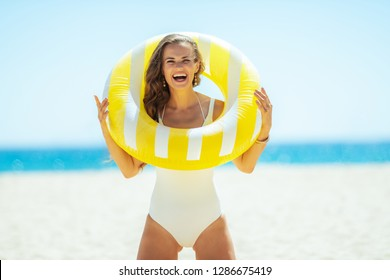 happy young woman in white swimwear with yellow inflatable lifebuoy on the seacoast. quiet vacation heaven. getting vitamin D after long winter months. spending hours at the beach. healthy hair