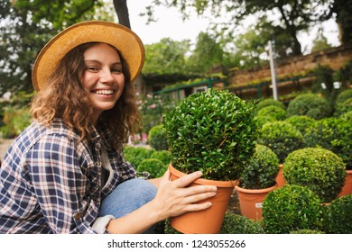 Happy young woman working in a greenhouse, holding a flower pot